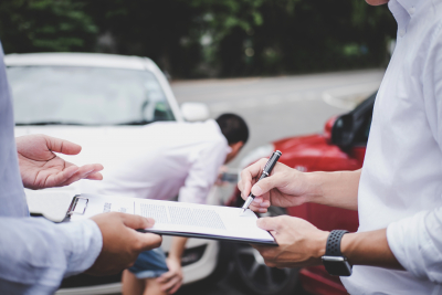 insurance agent examine damaged car and customer filing signature on report claim form